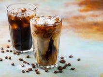 El café de hielo en un vidrio alto con crema vertió encima y los granos de café Bebida fría del verano en un fondo oxidado azul c Foto de archivo