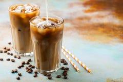 El café de hielo en un vidrio alto con crema vertió encima y los granos de café Bebida fría del verano en un fondo oxidado azul c Fotografía de archivo libre de regalías