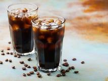El café de hielo en un vidrio alto con crema vertió encima y los granos de café Bebida fría del verano en un fondo oxidado azul c Fotografía de archivo