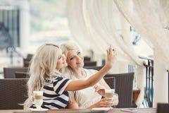 El café de la bebida de dos muchachas y utiliza el teléfono Fotos de archivo libres de regalías