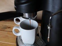 El café de la máquina del café se vierte en las tazas blancas, primer Imagen de archivo libre de regalías