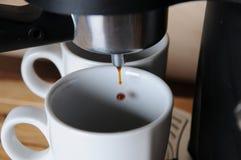 El café de la máquina del café se vierte en las tazas blancas, primer Fotografía de archivo