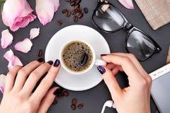 El café de la mañana con las galletas, manos del ` s de las mujeres sostiene una taza de café en la tabla fotos de archivo libres de regalías