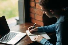 El café de trabajo y de consumición del estudiante en un café y anota algo en el cuaderno Prepárese para un examen fotos de archivo