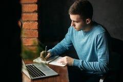 El café de trabajo y de consumición del estudiante en un café y anota algo en el cuaderno Prepárese para un examen foto de archivo libre de regalías