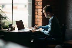 El café de trabajo y de consumición del estudiante en un café y anota algo en el cuaderno Prepárese para un examen imagen de archivo