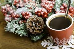 El café, el copo de nieve y la Navidad de la taza enrruellan con los conos del pino Imágenes de archivo libres de regalías