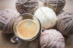 El café, el hilado de las agujas que hace punto, beige y blanco están en la tabla fotografía de archivo libre de regalías