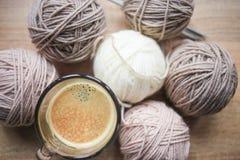 El café, el hilado de las agujas que hace punto, beige y blanco están en la tabla fotos de archivo libres de regalías
