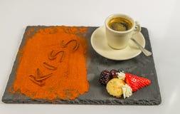 El café en una taza da fruto y el beso de la palabra en la placa de piedra negra Imagenes de archivo