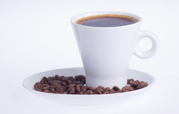 El café en una taza en un platillo cubierto con café sea Fotos de archivo libres de regalías