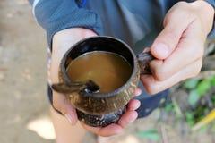 El café en el vidrio de cáscaras naturales del coco Foto de archivo