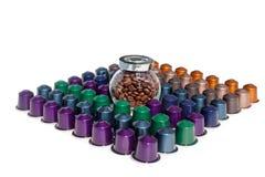 El café encapsula diverso tarro del color y de cristal con los granos de café en el fondo blanco aislado foto de archivo libre de regalías