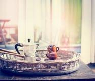 El café express fijó con las tazas de café, las habas y el pote del café en el café dulce en travesaño de la ventana Fotos de archivo