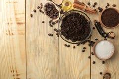 El café hecho en casa friega en la cara y el cuenco del cuerpo y los diversos ingredientes para hacer friegan en una tabla de mad foto de archivo libre de regalías