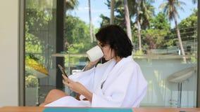 El café hermoso de la bebida de la mujer joven en terraza del chalet y hace el selfie El viaje relaja concepto del balneario