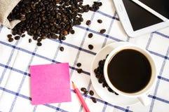 El café, los granos de café, los teléfonos, los lápices y los cuadernos están en el escritorio foto de archivo