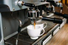 El café que hace la máquina vierte la dosis del cafeína de las tazas imágenes de archivo libres de regalías