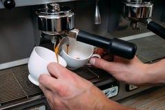 El café que hace la máquina vierte la dosis del cafeína de las tazas Imagen de archivo