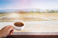 El café sólo en la taza blanca con el cielo azul y el arroz colocan Foto de archivo libre de regalías
