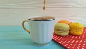 el café se vierte en una taza, cámara lenta del macaron almacen de metraje de vídeo