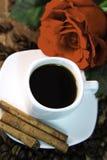 El café, subió, las habas y canela en el escritorio de madera Foto de archivo libre de regalías