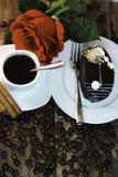 El café, torta, canela, habas y subió en el escritorio de madera Foto de archivo