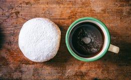El café y krapfen con el azúcar de polvo, dos, la visión superior y el fondo aislado, de madera imagen de archivo