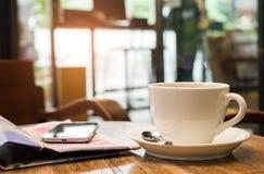 El café y un teléfono elegante están en el periódico Imagenes de archivo