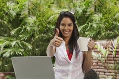 El café de consumición de la mujer, usando un ordenador portátil y el mostrar los pulgares suben el si Imagen de archivo