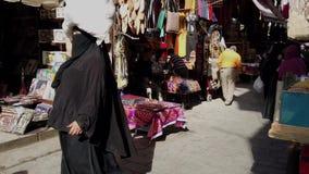 El Cairo, Egipto - 2019-05-03 - calle ocupada de Bizaare con la mujer en el paquete que lleva de Hijab en la cabeza almacen de video