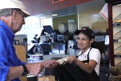 El cajero toma el dinero Imágenes de archivo libres de regalías