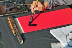 El calígrafo da la escritura del jeroglífico chino Fotos de archivo