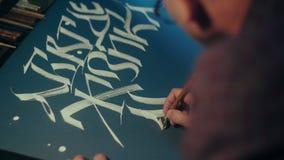 El calígrafo escribe la pluma de la lona Alfabeto eslavo Tinta blanca en el papel negro almacen de metraje de vídeo