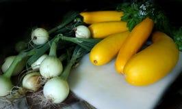 El calabacín de la calabaza amarilla y las cebollas verdes mienten en una tabla de cortar Foto de archivo libre de regalías