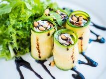 El calabacín rueda con queso del mascarpone, las nueces, la ensalada verde y la salsa de soja Fotos de archivo
