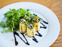 El calabacín rueda con queso del mascarpone, las nueces, la ensalada verde y la salsa de soja Imágenes de archivo libres de regalías