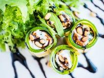 El calabacín rueda con queso del mascarpone, las nueces, la ensalada verde y la salsa de soja Imagenes de archivo