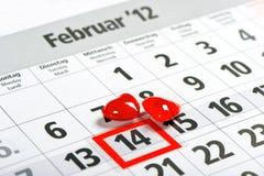El calendario con la marca roja el 14 de febrero y el rojo oyen Imágenes de archivo libres de regalías