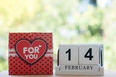 El calendario de madera, el 14 de febrero, consiste en una caja de corazones rojos que se escriban para usted, colocada de lado a imagen de archivo