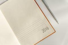 El calendario 2016 y la astilla del organizador de la oficina del Año Nuevo ballpen Fotos de archivo libres de regalías
