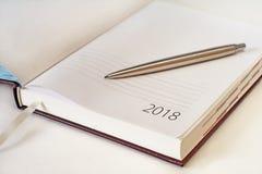 El calendario 2018 y la astilla del organizador de la oficina del Año Nuevo ballpen Sele Foto de archivo libre de regalías