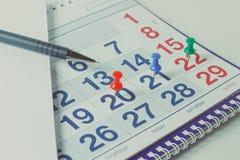 El calendario y la pluma de pared, los días importantes se marcan con los knops fotos de archivo