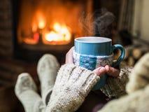 El calentarse y chimenea cercana relajante Imagenes de archivo