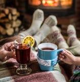El calentarse y chimenea cercana relajante con una taza de bebida caliente Imagen de archivo libre de regalías