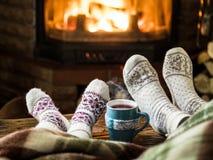 El calentarse y chimenea cercana relajante con una taza de bebida caliente foto de archivo libre de regalías