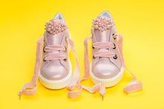 El calzado para las muchachas o las mujeres adornadas con la perla gotea Zapatos lindos en fondo amarillo Concepto cómodo del cal Imagen de archivo