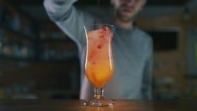 El camarero añade el sirop al cóctel colorido en la cámara lenta, haciendo los cócteles en una barra, bebida del alcohol, par metrajes