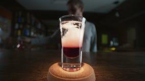El camarero añade el sirop del gimoteo al tiro acodado con el licor y la ginebra rojos en la cámara lenta, haciendo los cóctel almacen de video