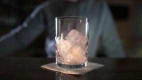 El camarero añade un poco de hielo al vidrio antes de hacer el cóctel, bebida del alcohol, haciendo bebidas frías frescas en una  almacen de metraje de vídeo